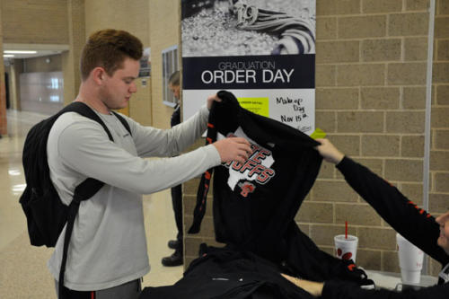 Dale Jones, 12, purchases a football playoff shirt during his lunch. Students are encouraged to wear the shirt to the game on Friday. Shirts can be bought for $20 and there is a limited supply available. (Landry Pedroza photo)