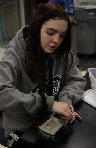 Simone Nelson, 12, sands her hand-made Christmas ornament. Art club finished glazing ornaments today after school. Shortly after, they started on a new project where they will create a mural using watercolors to create feathers. (Maija Miller Photo)
