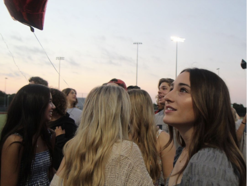 During the balloon release at Senior Sunrise Aug 20, Presli Wallace, 12, watches classmates celebrate their last year at Legacy. The student council provided Chick-fil-a breakfast for students while parents helped staff set up for this event. (Landri Hargrove Photo)