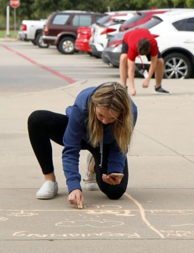 During AP Environmental Science, Brenly Childers, 11, uses chalk to draw ecosystem services. APES is an optional science class offered to juniors and seniors, in order to help complete the required number of science credits to graduate. (Madison Moyer Photo)