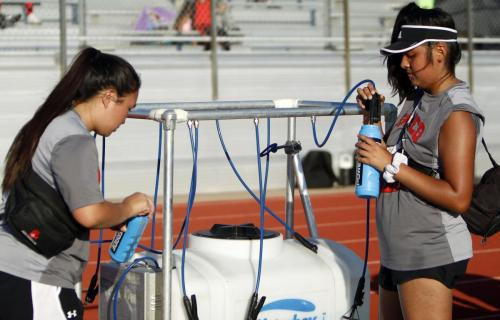 Trainers, Abigail Ling, 10, and Cristina Santos, 10, fill up water bottles for the JV B football team. JV B won against Mansfield High School 26-14. (Samantha Freeman Photo)