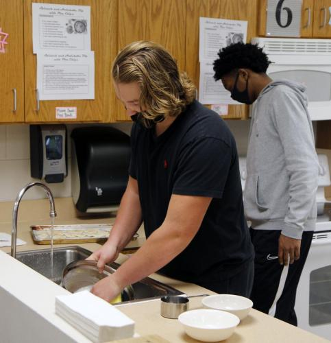 Junior Sterling Cox washes dishes after making pita chips for a cooking lab. Students in Intro to Culinary will be making Christmas cookies Dec. 8 and 9. (Samantha Freeman Photo)