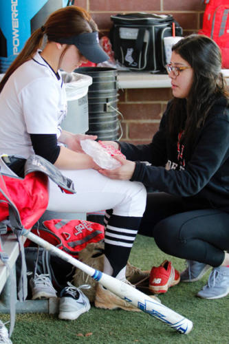 Trainer Katelyn Finch, 10, ices Daylin Childers', hand after getting hit with the ball during the varsity softball game. Legacy beat Seguin High School, 15-0. (Madison Gonzales photo)
