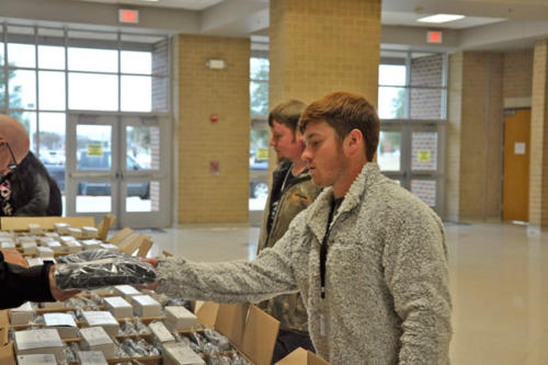 Corbin Franklin, 12, picks up his cap and gown order during A lunch. Seniors were able to pick up their cap and gowns from Josten's during lunches. (Landry Pedroza photo)