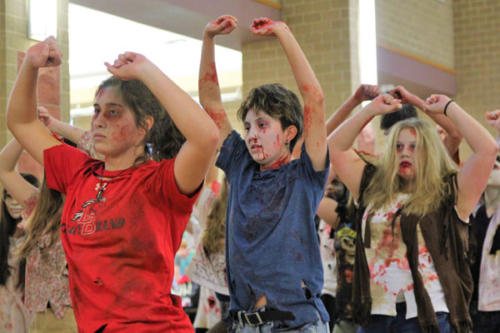 "Kate Claburn, 10, Zoe Quintana, 10, and Kathryn Pedroza, 12, perform a dance routine to ""Thriller"" during a flash mob. Musical theater performed during all lunches as a fun way to celebrate Halloween. (Kassidy Duncan photo)"
