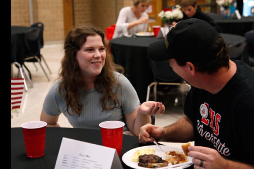 Molly Rea, 12, tells her father a story as he eats during the Veteran's Day Lunch. Student Council hosts this luncheon annually to honor and show gratitude for the service of faculty members and students' family members.  (Kassidy Duncan photo)